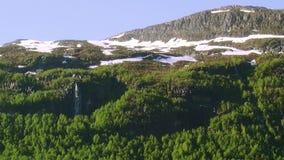 Панорамный взгляд гор покрыл древесные зелени, снег на верхних частях в дне лета солнечном Водопад Природа сток-видео