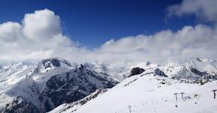 Панорамный взгляд на наклоне лыжи и пасмурных горах на славном дне солнца Стоковые Фотографии RF