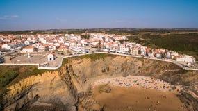Панорамный взгляд Zambujeira de mar и пляжа с антенной людей отдыхающих Стоковые Фото
