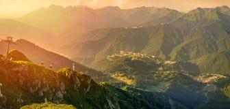 Панорамный вид захода солнца летом от вершины ряда Aibga к лыжному курорту Роза Khutor Фуникулер стоковое фото