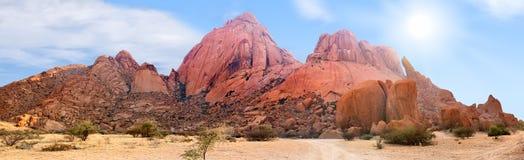 Панорамный вид ряда гор Spitzkoppe на голубом небе, облаках и яркой предпосылке солнца, ландшафте панорамы горы, Намибии стоковая фотография rf