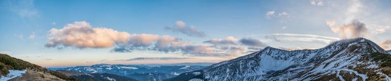 Панорамный пейзаж гор и долины в заходе солнца освещают Стоковые Изображения