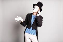 Пантомима человека говоря на его сотовом телефоне Концепция дня дурачка в апреле Стоковая Фотография