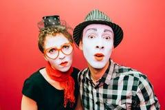 2 пантомимы представляя против красной предпосылки стены Стоковое Фото