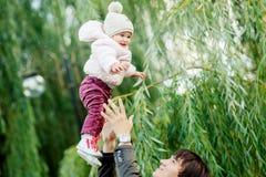 Папа бросает вверх девушку в парке осени стоковые изображения rf