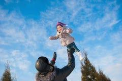 Папа бросает вверх дочь младенца в зиме против голубого неба, образе жизни, зимних отдыхах стоковые фотографии rf