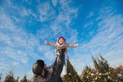 Папа бросает вверх дочь младенца в зиме против голубого неба, образе жизни, зимних отдыхах стоковое изображение