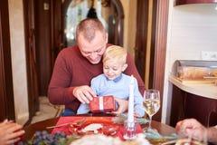 Папа давая красный подарок к маленькому сыну на праздничной предпосылке Концепция подарков на рождество семьи Стоковое Фото