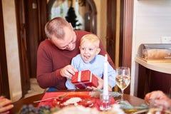 Папа давая красный подарок к маленькому сыну на праздничной предпосылке Концепция подарков на рождество семьи Стоковые Фото