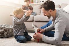 Папа дает его подарок сына в красной коробке дома стоковое фото