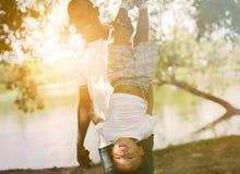 Папа держа сына вверх ногами в парке под солнечным светом стоковое изображение rf