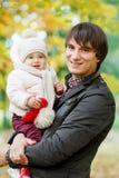 Папа держит дочь на предпосылке ландшафта осени стоковые фотографии rf