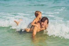 Папа играет с его сыном в море стоковое изображение rf