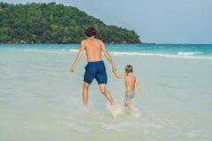 Папа играет с его сыном в море стоковая фотография rf