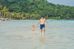 Папа играет с его сыном в море стоковое изображение