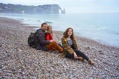 Папа и 2 дочери сидя на пляже Etretat стоковая фотография