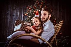 Папа и дочь держа подарочные коробки пока сидящ совместно на кресло-качалке около рождественской елки дома стоковые изображения rf