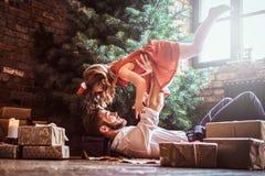 Папа и дочь имеют потеху совместно пока лежащ на поле, окруженном подарками около рождественской елки стоковая фотография