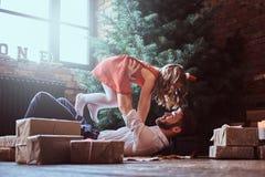 Папа и дочь имеют потеху совместно пока лежащ на поле, окруженном подарками около рождественской елки стоковые изображения rf