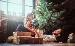 Папа и дочь лежа на поле, окруженном подарками около рождественской елки стоковое фото rf