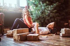 Папа и дочь лежа на поле, окруженном подарками около рождественской елки стоковое изображение