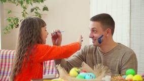 Папа и дочь пятнают друг друга стороны с голубой краской для крася яя На таблице корзина с пасхальными яйцами сток-видео
