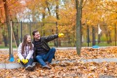 Папа и дочь сидят в парке на обочине после сбора упаденных листьев стоковые изображения