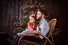 Папа и дочь сидя совместно на кресло-качалке около рождественской елки дома стоковое изображение