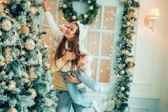 Папа и дочь украшают рождественскую елку внутри помещения за утро до Xmas Стоковое Изображение RF