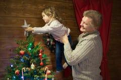 Папа и дочь украшают рождественскую елку Стоковая Фотография