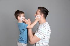 Папа и его маленький сын применяясь бреющ пену стоковая фотография rf