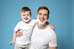 Папа и его маленький сын с брить пену на сторонах стоковые изображения rf