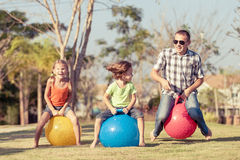 Папа и дети играя на лужайке перед домом стоковое изображение