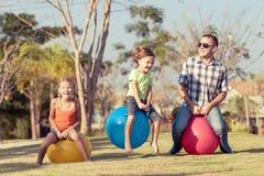 Папа и дети играя на лужайке перед домом стоковое фото rf