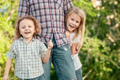 Папа и дети играя около дома на времени дня стоковое фото