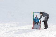 Папа идет при его сын в зиме и свернутый вниз холму Стоковое Изображение RF
