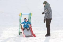 Папа идет при его сын в зиме и свернутый вниз холму Стоковые Фото