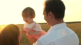 Папа и мама играя с маленькой дочерью в ее оружиях на заходе солнца семья идет с ребенком на заходе солнца игра отца акции видеоматериалы