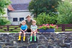 Папа и 2 мальчика маленького ребенка сидя совместно на каменном мосте стоковые фото