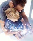 Папа и мальчик играя совместно на таблетке ПК мобильного компьютера, отдыхая в современном доме Детство мечтает концепция значков стоковые изображения rf