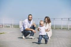 Папа и младенец мамы семьи счастливые с улыбками совместно в парке o стоковые фото