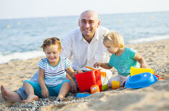Папа и дочери на пляже стоковое изображение
