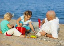Папа и дочери на пляже Стоковые Изображения