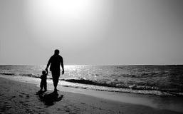 Папа и ребенок на пляже на на заходе солнца стоковые изображения