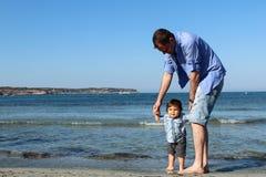 Папа и ребёнок на песчаном пляже Стоковое фото RF