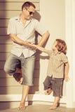Папа и сын играя около дома стоковое фото