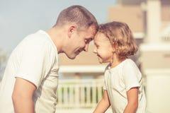 Папа и сын играя около дома стоковое изображение