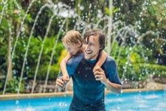 Папа и сын имеют потеху в бассейне стоковая фотография rf