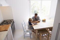 Папа и сын используют таблетку в кухне, повышенном взгляде от входа Стоковая Фотография RF