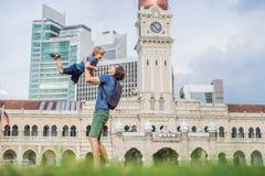 Папа и сын на предпосылке квадрата Merdeka и здания Abdul Samad султана Путешествовать с концепцией детей стоковое фото rf